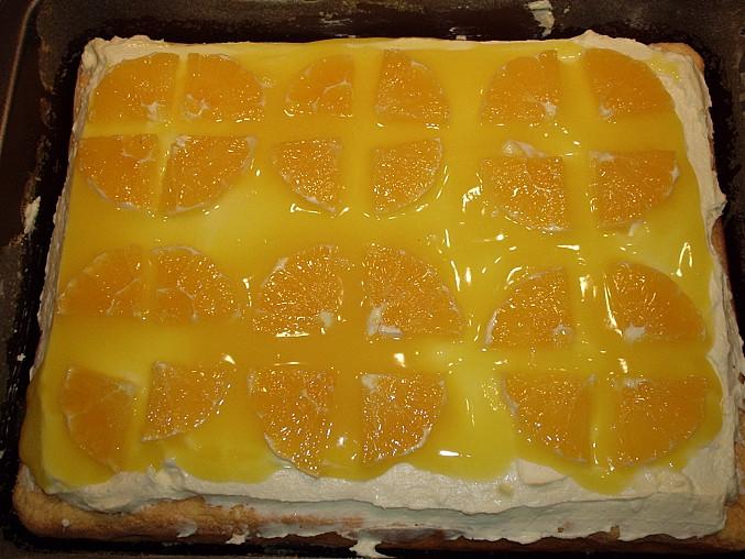 Piškotová buchta s tvarohem a pomerančovým želé, na krém rozetřeme polovinu želé a ozdobíme plátky pomeranče