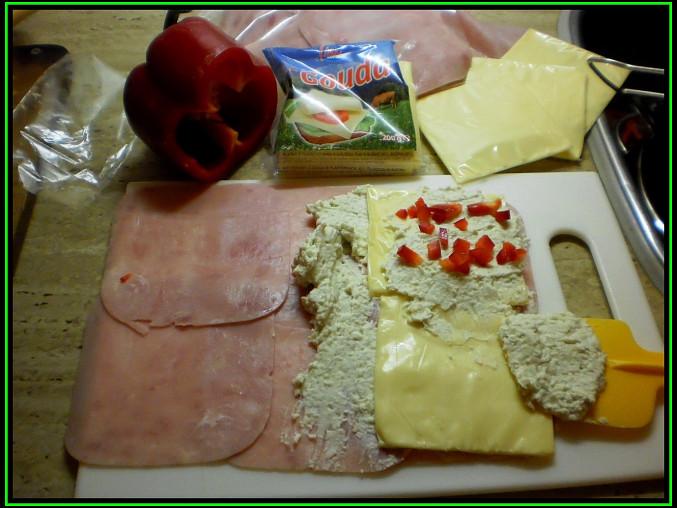 Šunková rolka na chlebíčky, šunku potřeme náplní,poklademe plát.sýrem,opět natřeme a posypeme paprikou