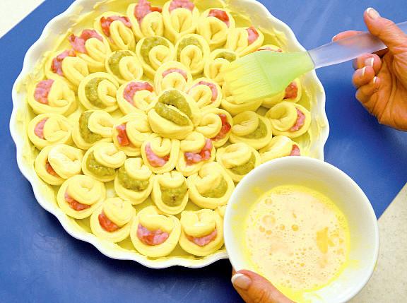 Buchtičkový koláč k uždibování, Formu vyplňte v kruzích od obvodu ke středu a náplně střídejte. Po dokynutí potřete povrch rozšlehaným vejcem a koláč upečte