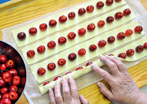 Točený třešňový dort, Na každý pruh uložte středem řadu vypeckovaných třešní s mezerami o velikosti poloviny plodu a do těsta celou opatrně zabalte