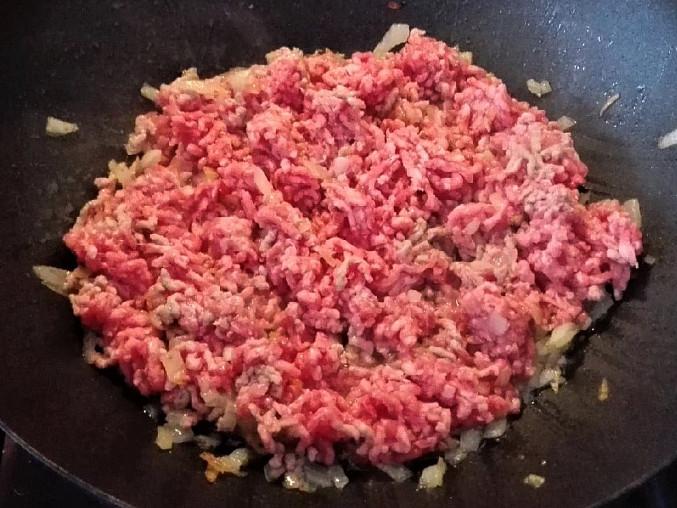 Přidáme mleté maso a rozdělíme ho vařečkou.