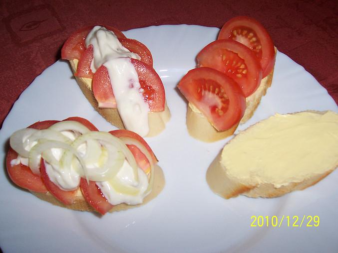 plátky veky namazat máslem, poklást rajčaty, polít tatarkou, ozdobit cibulí