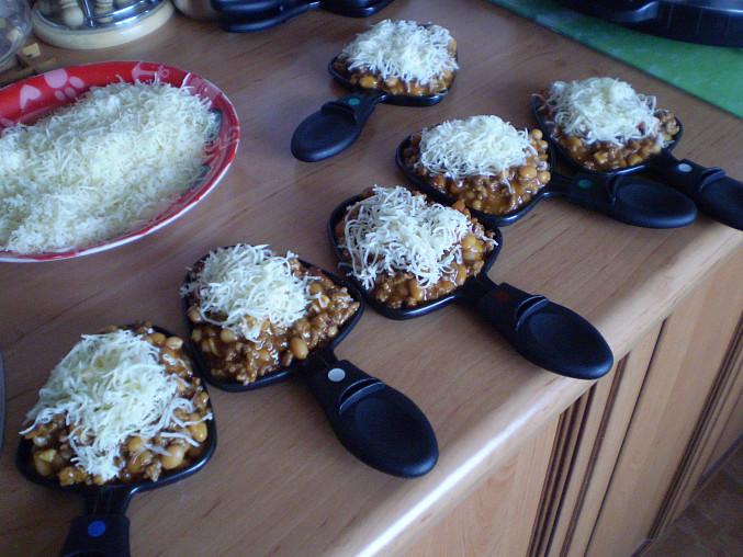 Dáme do zapékacích mističek a navrstvíme strouhaný sýr